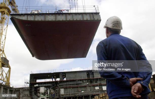 Workers at the Alstom Chantiers de L'Atlantique ship yard in Saint Nazaire Brittany France watch as the keel laying ceromony takes place on the Queen...