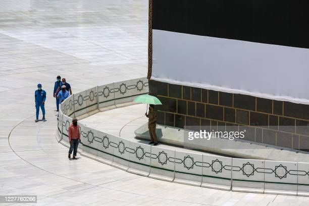 Workers at the Grand Mosque complex in Saudi Arabia's holy city of Mecca, mask-clad due to the COVID-19 coronavirus pandemic, work around the Kaaba,...