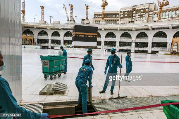 Workers at the Grand Mosque in Saudi Arabia's holy city of Mecca lay out lines to direct pilgrims as part of distancing measures due to the COVID19...