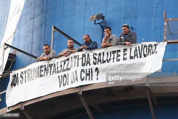 Workers at the Ilva steel mill in Taranto unfurl a banner as they demonstrate against the planned partial closure of the plant on September 27 2012 A...