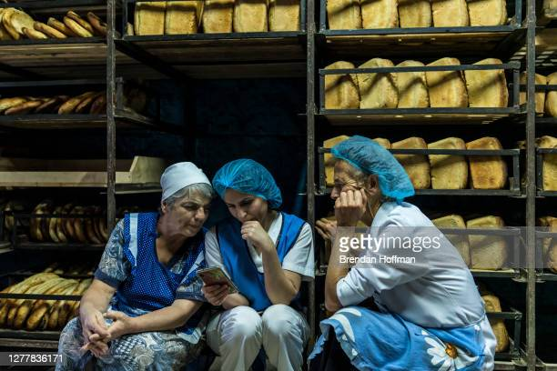 Workers at the Karavay bread factory watch an online video report about the ongoing war during a break from baking bread for members of the Armenian...
