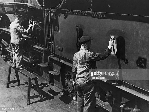 Workers at the railway sheds in Derby paint out the old LMS signs after the nationalisation of Britain's railways, 25th May 1948. The 'LMS' will be...