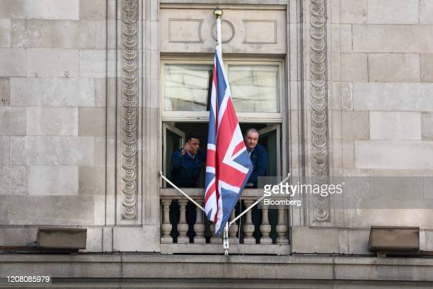 Workers at the shuttered The Ritz hotel bring in a British Union Flag also known as Union Jack in London UK on Tuesday March 24 2020 The UK is in...