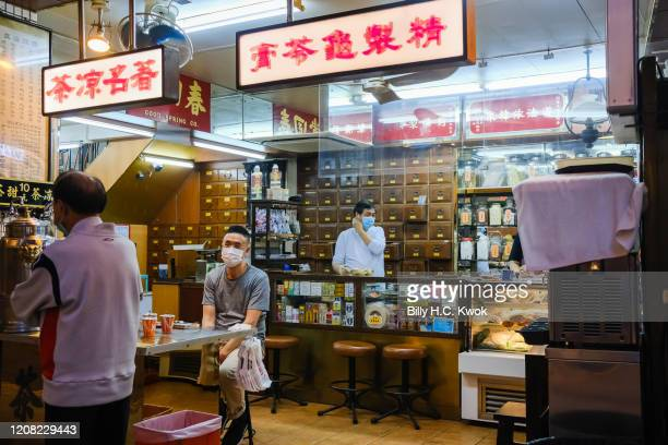 Workers at the traditional Chinese medicine shop wear face masks as a precaution against the spread of Coronavirus during a coronavirus outbreak on...