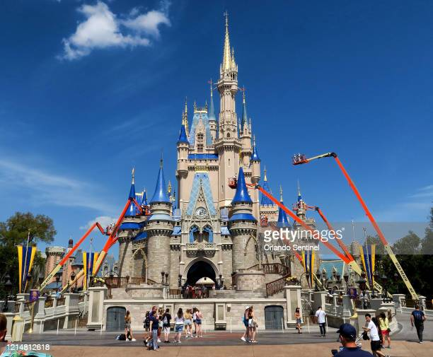 Workers at Walt Disney World paint Cinderella Castle in the Magic Kingdom in Lake Buena Vista Fla on March 12 2020
