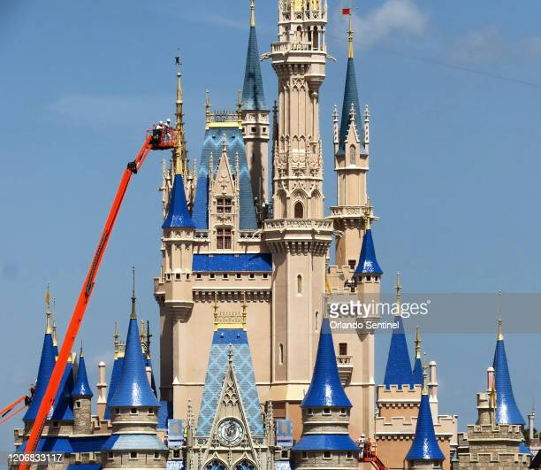 Workers at Walt Disney World paint Cinderella Castle in the Magic Kingdom on Thursday March 12 2020 in Lake Buena Vista Fla The iconic castle is...