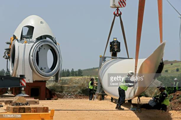 Workers attach a blade to the hub during construction of a new wind turbine as part of the Valley of Tears wind turbines farm project on May 19, 2020...