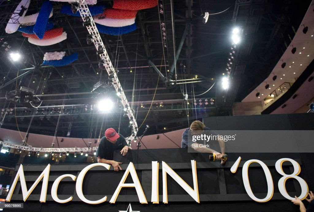 Workers attach a McCain '08 sign to the side of th emain camera stand on floor of the Republican National Convention at the Excel Center in St. Paul, Minn., on Monday, Sept. 1, 2008.