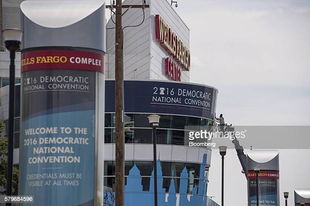 Workers attach a sign to the front of the Wells Fargo Center ahead of the Democratic National Convention in Philadelphia US on Sunday July 24 2016 A...
