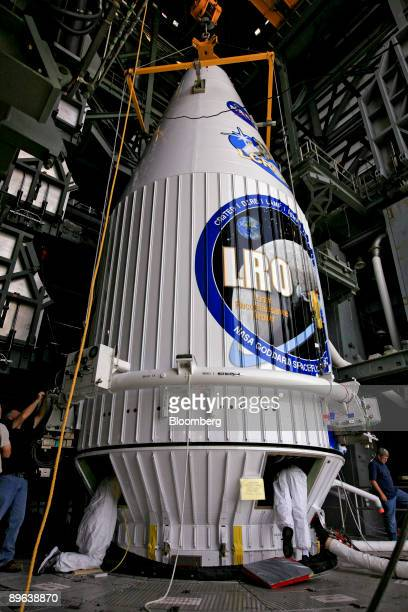 Workers attach NASA's Lunar Reconnaissance Orbiter and Lunar Crater Observation Sensing Satellite to an Atlas V rocket inside the mobile service...