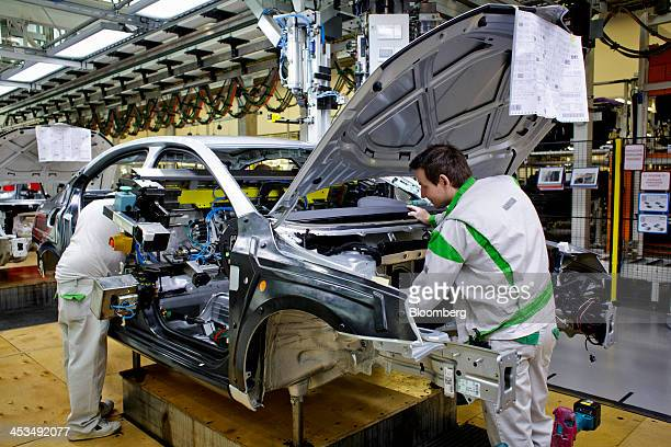 Workers attach parts to the body shell of a Skoda Octavia automobile on the production line at the Skoda Auto AS plant in Mlada Boleslav Czech...
