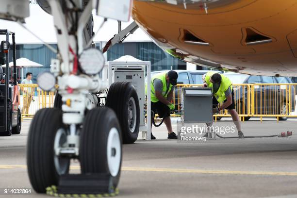 Workers attach power cables near a prototype of the Embraer SA E190 E2 passenger aircraft on display during a media preview day at the Singapore...