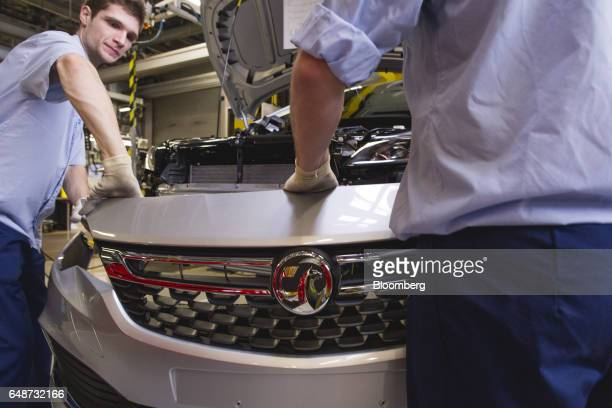 Workers attach the front grill to a Vauxhall Astra vehicle on the production line at the Opel automobile plant in Gliwice Poland on Monday March 6...
