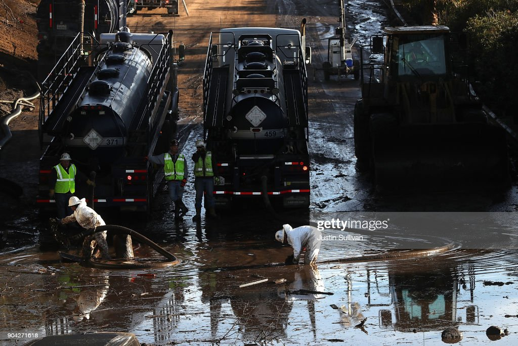 Workers attempt to drain a section of Highway 101 that was flooded following a mudslide on January 12, 2018 in Montecito, California. 17 people have died and hundreds of homes have been destroyed or damaged after massive mudslides crashed through Montecito, California early Tuesday morning.