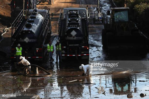 Workers attempt to drain a section of Highway 101 that was flooded following a mudslide on January 12 2018 in Montecito California 17 people have...