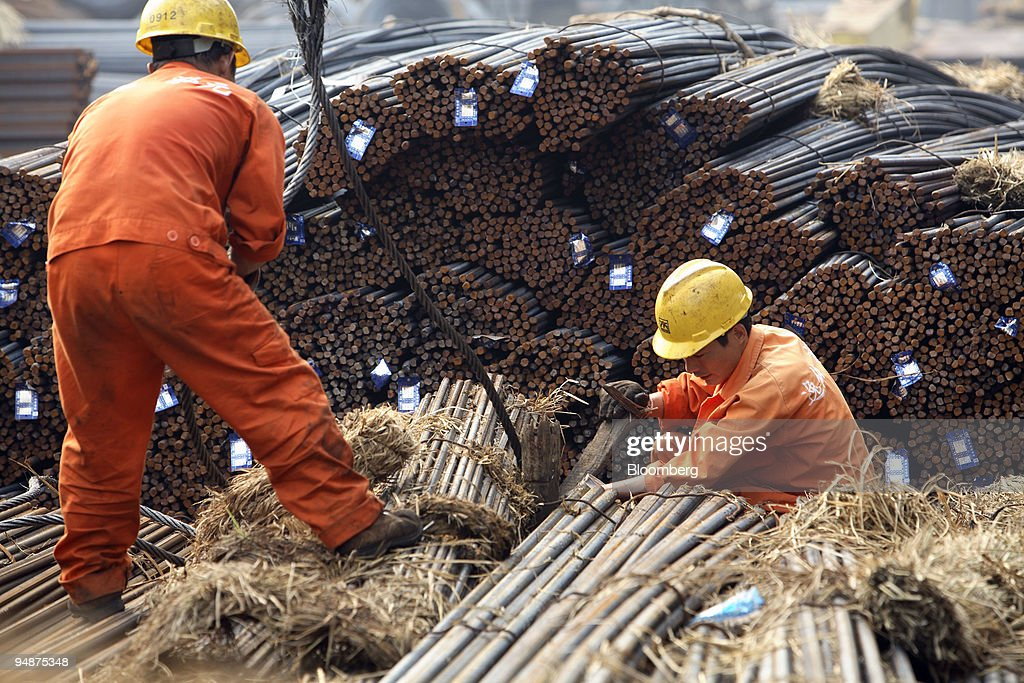 workers attempt to hoist up a load of steel rebar at a steel trading stockyard in