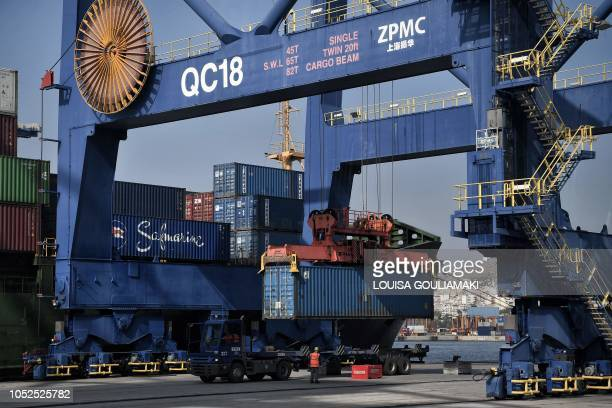 Workers attend container loading on a ship at the new container terminal in the port of Piraeus on October 18, 2018. - Chinese shipping giant Cosco...