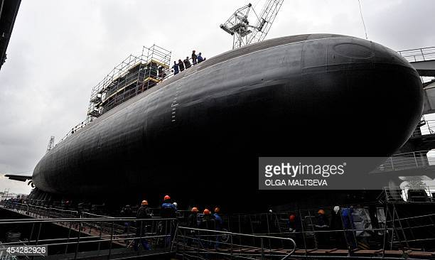 Workers attend the launching ceremony of the Russian dieselelectric attack submarine Stary Oskol on Admiralty Shipyard in Saint Petersburg on August...