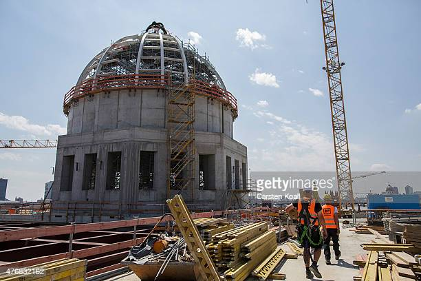 Workers attend the toppingout ceremony for the Humboldt Forum on June 12 2015 in Berlin Germany The ambitious project located in the city center will...