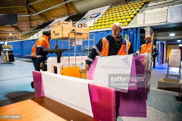 Workers begin to errect voting booths at an indoor sports center that will serve as a center for citizens to vote in the House of Representatives...