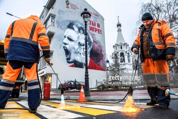TOPSHOT Workers blowtorch the paint of a pedestrian crossing in front of an advertisement for the FIFA World Cup 2018 sponsor Alfa Bank reading 'You...