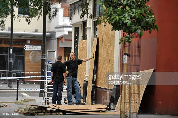 Workers board up a damaged shop front on Brixton High Street following a second night of disturbances in London on August 8 2011 Police said Monday...