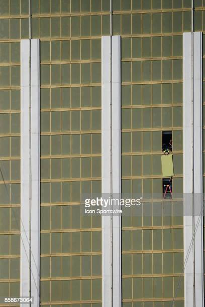 Workers board up one of the windows at Mandalay Bay Resort and Casino in Las Vegas on October 6 where a gunman fired during a mass shooting that...
