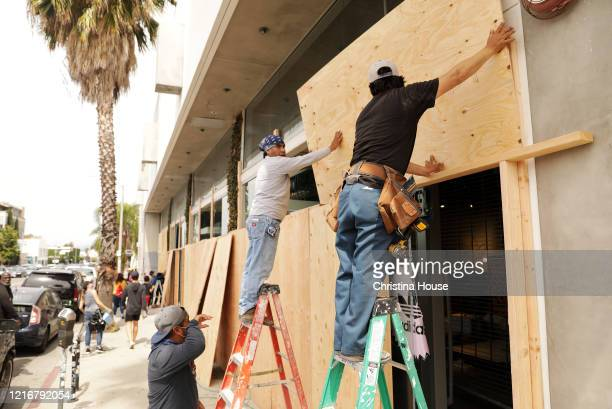 Workers board up the Adidas store on Melrose Avenue on Sunday May 31 2020