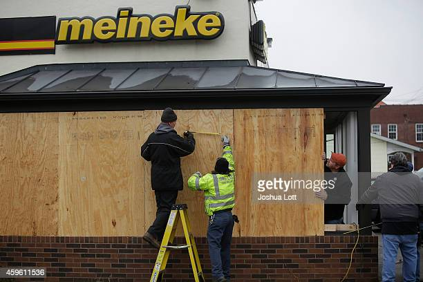 Workers board up windows at a Meineke auto repair shop after demonstrators protesting the shooting death of Michael Brown smashed the windows...