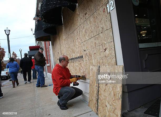 Workers board up windows at a restaurant near the Buzz Westfall Justice Center on November 24 2014 in Clayton Missouri A St Louis County grand jury...