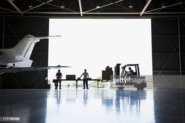 Workers, boxes and forklift in hangar