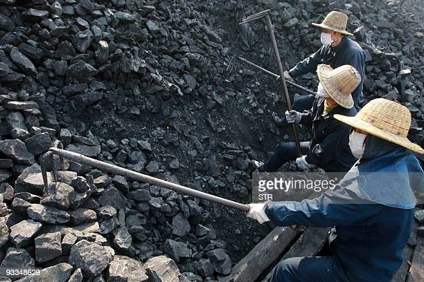 Workers break the coal into smaller pieces for processing at a mine yard in Huaibei central China's Anhui province on November 24 2009 More deadly...