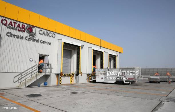 Workers bring freshly imported products offloaded from a Qatar Airways cargo plane to be checked at a climate control centre at the Hamad...