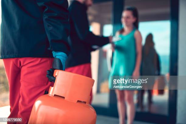 workers bringing gas cylinder to lady customer - butane stock pictures, royalty-free photos & images