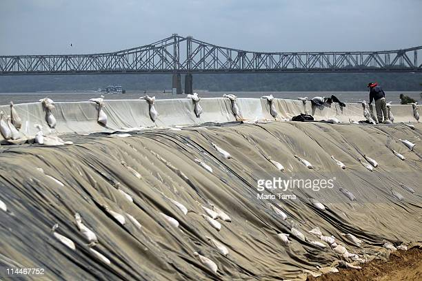Workers build a 16foot makeshift levee to protect the 100yearold JM Jones Lumber Company on the edge of the flooding Mississippi River on May 20 2011...