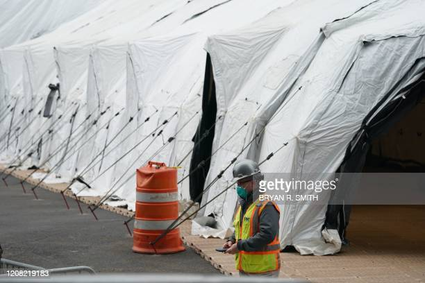 Workers build a makeshift morgue outside of Bellevue Hospital to handle an expected surge in Coronavirus victims on March 25 2020 in New York...
