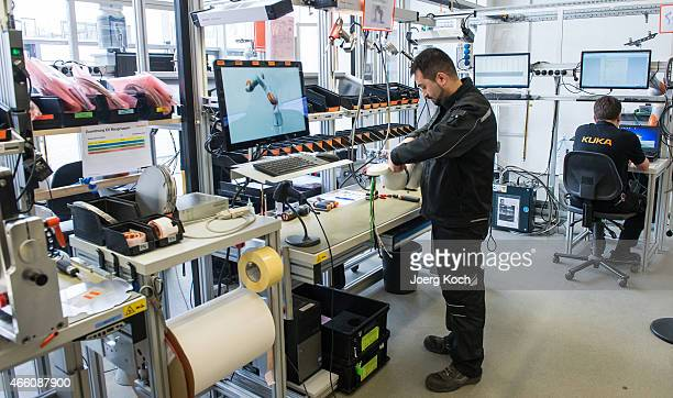 Workers build a robotic arm at the KUKA industrial robotics factory on March 13 2015 in Augsburg Germany Germany's exportdriven economy has fared...