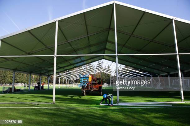 Workers build a temporary field hospital on a soccer field for people ill with the novel coronavirus so they can isolate and recover on March 19,...