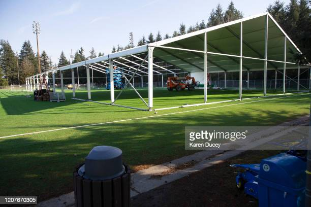 Workers build a temporary field hospital on a soccer field for people ill with the novel coronavirus so they can isolate and recover on March 19 2020...