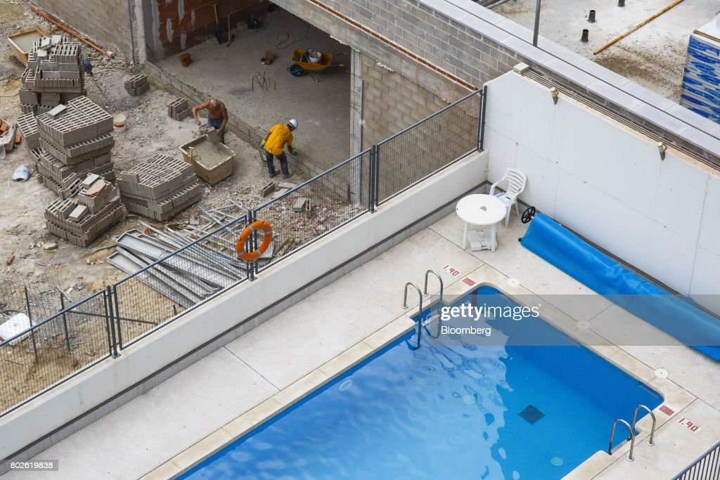 Workers build a wall at a construction site near a rooftop ...