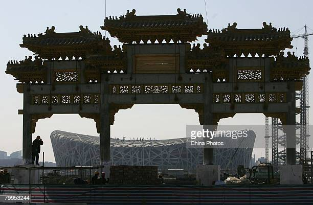 Workers build an ancient style Pailou or symbolic honorific gate in front of the National Stadium on February 23 2008 in Beijing China As the last...