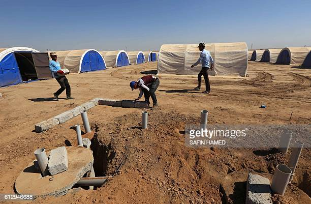 Workers build shelters to house civilians who are expected to flee the violence in the northern city of Mosul as a result of a planned operation to...