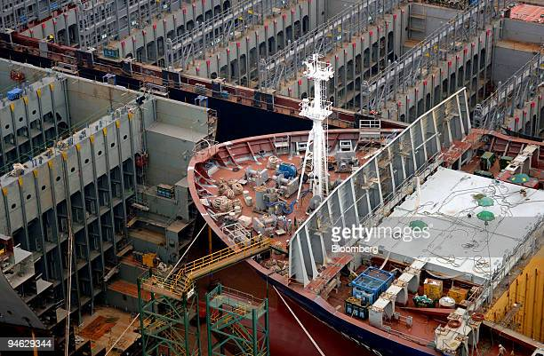 Workers build ships in a drydock at the Hyundai Heavy Industries Co's shipyard in the port of Ulsan South Korea Friday August 11 2006 Japan China and...