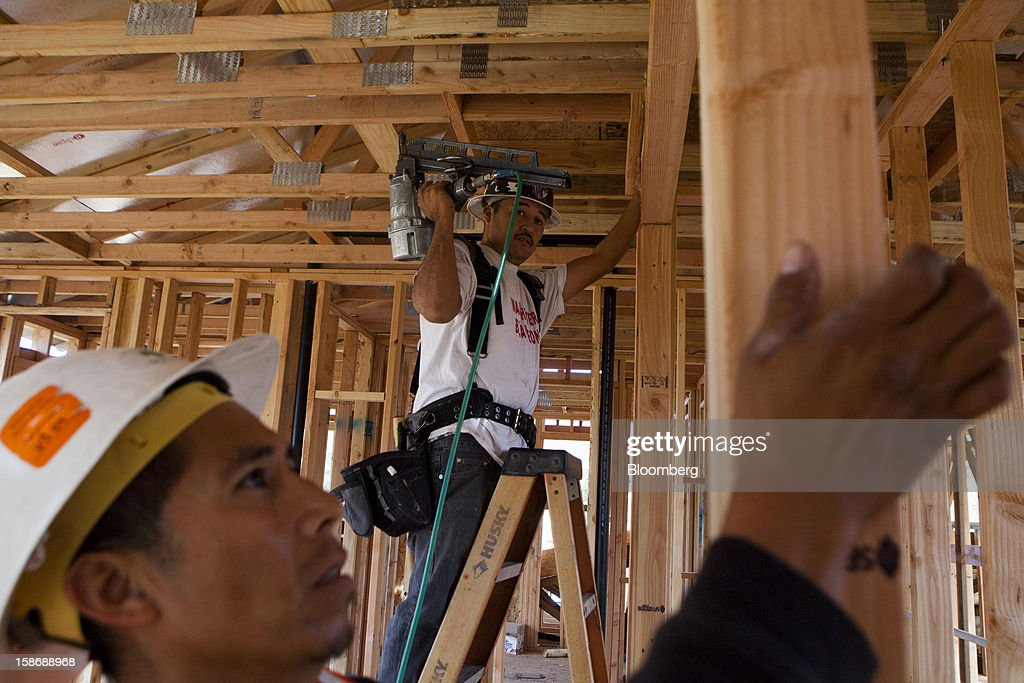 Workers build stud-framed walls in a house under construction at Davidson Communities LLC's Arista at The Crosby development in Rancho Santa Fe, California, U.S., on Friday, Dec. 21, 2012. New home sales climbed to a 380,000 annual rate in November, the most since April 2010, according to the median forecast of 60 economists surveyed by Bloomberg before Dec. 27 figures from the Commerce Department. Photographer: Sam Hodgson/Bloomberg via Getty Images