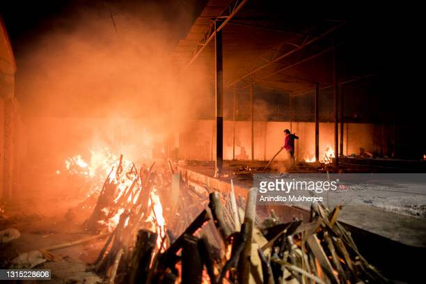 Workers can be seen at a crematorium where multiple funeral pyres are burning for patients who lost their lives to Covid-19 on April 29, 2021 in New...