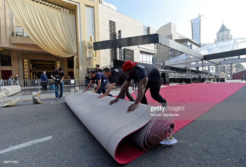 Workers Carlyon Prevost (R) Ernest Jauregui (C) and Eddie Padilla roll out the red carpet in preparation of 87th Annual Academy Awards at Dolby Theater February 18, 2015 in Hollywood, California.