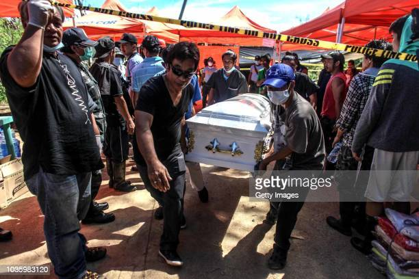 Workers carry a coffin of a victim killed by a landslide on September 19 2018 in Itogon Benguet province Philippines Dozens of people are feared to...