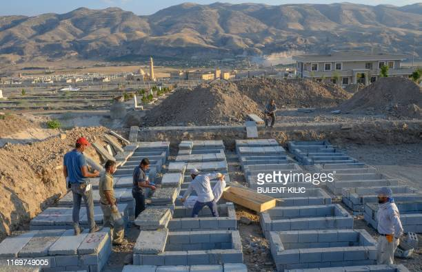 Workers carry a corpse in the new Hasankeyf cemetery after they transfered it from the old Hasankeyf in Hasankeyf at on the banks of the Tigris in...