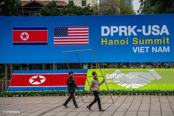 Workers carry a frame past a display board announcing the forthcoming DPRKUSA summit at the international media centre on February 24 2019 in Hanoi...