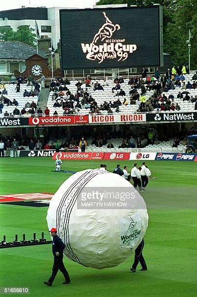 Workers carry a giant balloonfilled cricket ball onto the pitch during the brief opening ceremony for the 1999 Cricket World Cup at Lord's ground in...